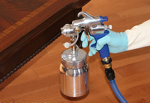 A lacquer paint sprayer in use